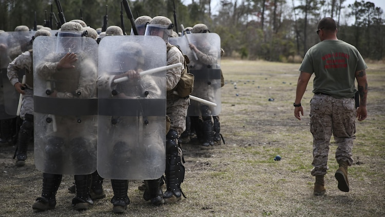"Staff Sgt. Shawn J. Dyer, the lead non-lethal weapons instructor with Expeditionary Operations Training Group, II Marine Expeditionary Force, observes the Marines of Battery and Golf Co., 2nd Battalion, 6th Marines, as they perform various riot control techniques during non-lethal weapons training aboard Camp Lejeune, N.C., March 24, 2015. ""The Marines here are doing really well,"" Dyer said. ""At first, it's difficult for an infantry unit to come here and get used to moving in close formations with the shields, but they're learning quickly."""
