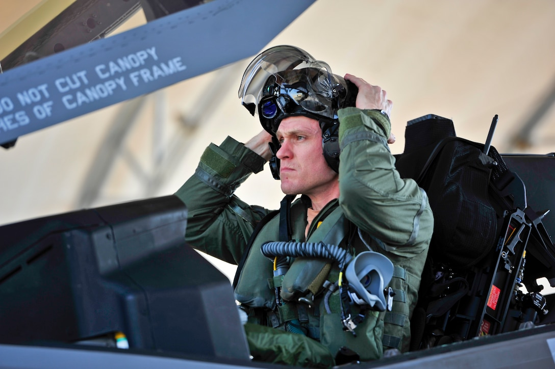 Royal Australian Air Force Squadron Leader Andrew Jackson, F-35 Lightning II student pilot, puts on his helmet before his first flight in an F-35A on Eglin Air Force Base, Fla., March 18, 2015. Jackson made history as the first Australian pilot to fly in the F-35A. The fifth-generation aircraft will meet Australia's future air combat and strike needs, providing a networked force-multiplier effect in terms of situational awareness and combat effectiveness. (U.S. Air Force photo/Staff Sgt. Marleah Robertson)