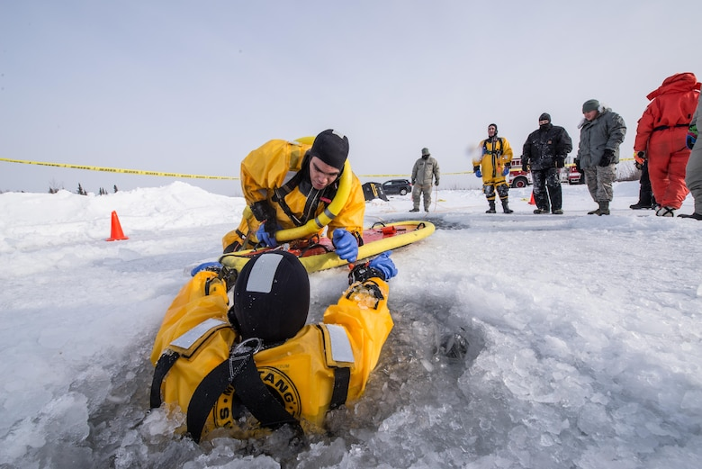 U.S. Air Force Airman 1st Class Israel Hernandez, a 354th Civil Engineer Squadron firefighter, prepares to rescue a simulated victim trapped in freezing water during training on Eielson Air Force Base, Alaska, March 12, 2015. Fire protection Airmen from the 354th CES train annually to practice rescuing a victim trapped in a broken part of a frozen lake. (U.S. Air Force photo by Staff Sgt. Joshua Turner/Released)