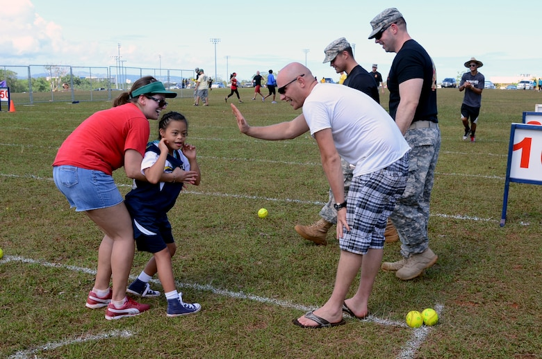 Team Andersen volunteers encourage a Special Olympic athlete at the softball throwing event at Okkodo High School in Dededo, Guam, March 21, 2015. More than 300 service members from all military branches assigned to units on Guam came together to support Special Olympic athletes in a variety of track and field events. (U.S. Air Force photo by Airman 1st Class Alexa Ann Henderson/Released)