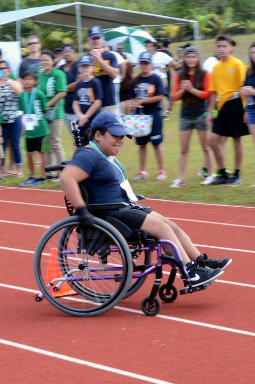 A Special Olympic athlete races through the wheelchair slalom event at Okkodo High School in Dededo, Guam, March 21, 2015. More than 300 service members from all military branches assigned to units on Guam came together to support Special Olympic athletes in a variety of track and field events. (U.S. Air Force photo by Airman 1st Class Alexa Ann Henderson/Released)