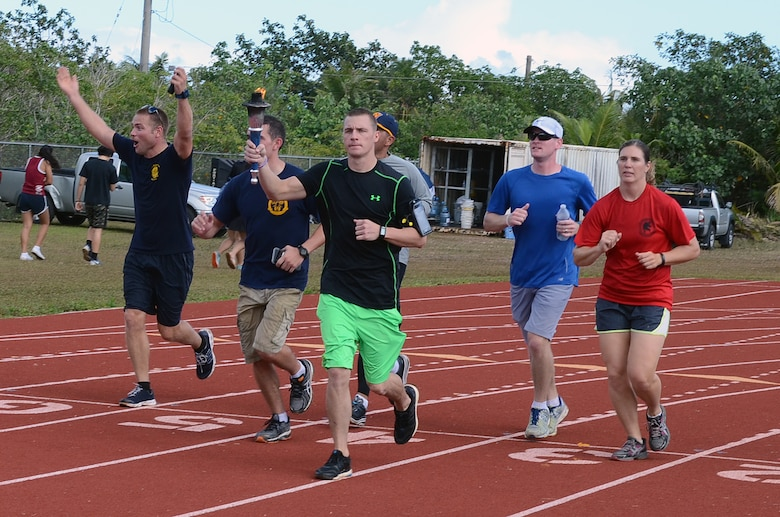 Staff Sgt. Eric Mattson, 554th RED HORSE Squadron, carries the Special Olympics Flame of Hope Torch at Okkodo High School in Dededo, Guam, March 21, 2015. More than 300 service members from all military branches assigned to units on Guam came together to support Special Olympic athletes in a variety of track and field events. (U.S. Air Force photo by Airman 1st Class Alexa Ann Henderson/Released)