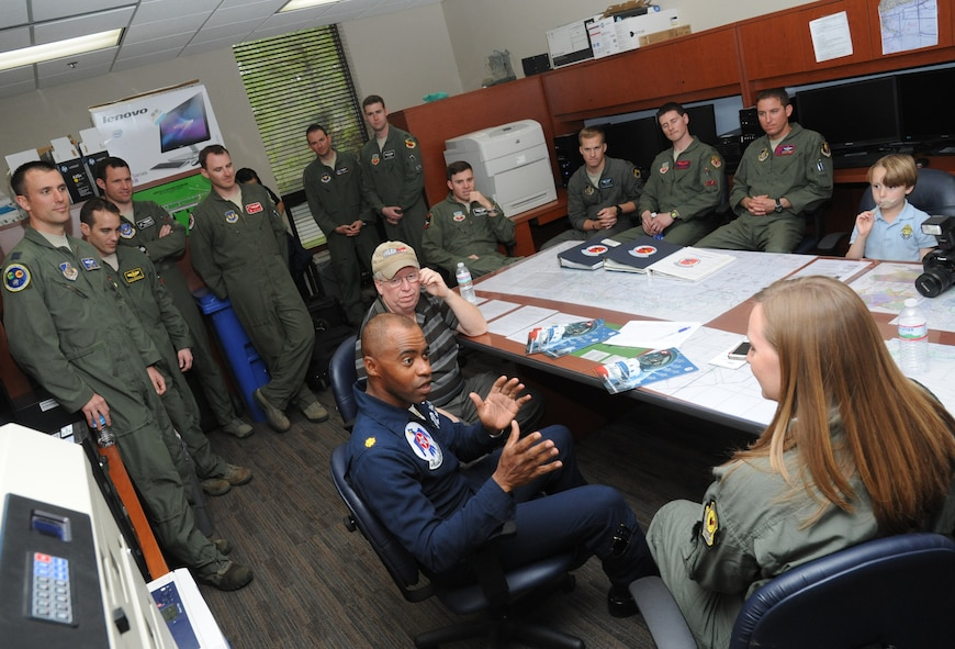 Maj. Darrick Lee, U.S. Air Force Thunderbirds public affairs officer number 12, briefs Meggan Gray, WLOX anchor, and Rodney Billingsby, WLOX camera operator, during flight training March 26, 2015, at Keesler Air Force Base, Miss.  The training was to prepare Gray for a media flight with the U.S. Air Force Thunderbirds March 27.  The Thunderbirds are headlining Keesler's 2015 Air Show/Open House to be held March 28-29.  (U.S. Air Force photo by Kemberly Groue)