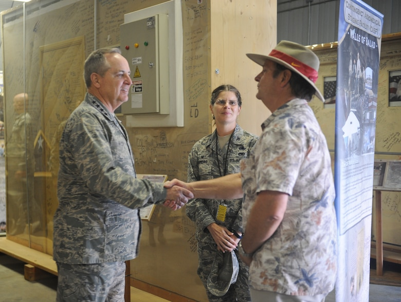 Air Force Chief of Staff Gen. Mark A. Welsh III shakes hands with Tommy Bledsoe, 309th Aerospace Maintenance and Regeneration Group business affairs representative while Col. Margaret Romero, 309th AMARG commander looks on at the Walls of Balad exhibit at Davis-Monthan Air Force Base, Ariz., March 25, 2015. The Walls of Balad are signed  by thousands of patients, service members and visitors of Joint Base Balad hospital, Iraq. (U.S. Air Force photo by Cheyenne Morigeau/released)