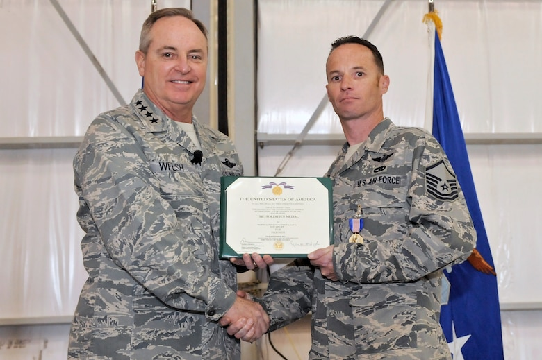 U.S. Air Force Chief of Staff Gen. Mark A. Welsh III and Master Sgt. Matthew Garcia, 55th Rescue Squadron special mission aviator, pose for a photo after a medal presentation at Davis-Monthan Air Force Base, Ariz., March 25, 2015. Welsh presented Garcia with the Soldier?s Medal for his act of heroism that saved the lives of two pilots who were injured after landing their helicopter on an improvised explosive device. (U.S. Air Force photo by Airman 1st Class Chris Drzazgowski/Released)