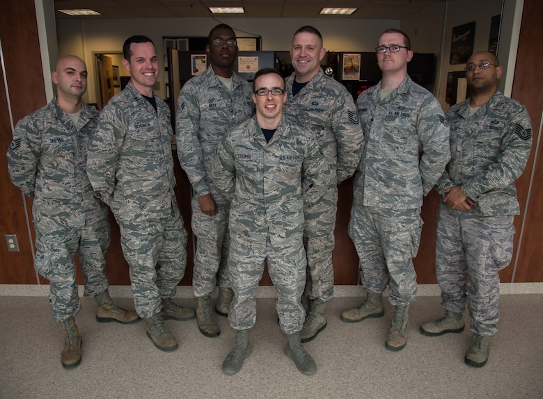 The 89th Operational Support Squadron/Operational Weather Squadron poses for a photo after being recognized and coined by the Col. Brad Hoagland, JBA/11th Wing commander, at the weather flight office on Joint Base Andrews, Md., March 13th, 2015. The 89 OSS/OSW is being recognized for correctly forecasted eight-out-of-eight winter weather system. (U.S. Air Force photo/Airman 1st Class Philip Bryant)