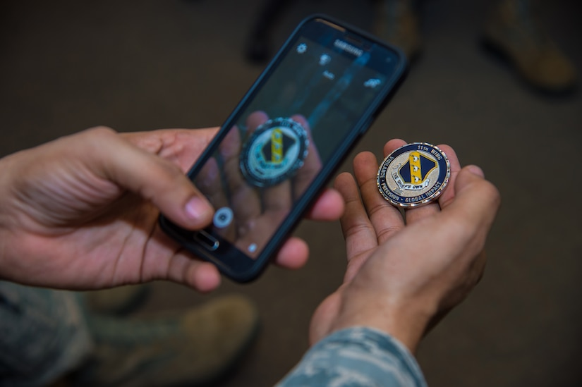 Tech. Sgt. Alfred Brooks, 89th Operational Support Squadron/Operational Weather Squadron airfield services NCO In-Charge, takes a photo of his new coin at the weather flight office on Joint Base Andrews, Md., March 13th, 2015. He took the photo with his phone with plans to share the news with friends and family. The 89 OSS/OSW was recognized by Col. Brad Hoagland, JBA/11th Wing commander, for correctly forecasted eight out of eight winter weather system. (U.S. Air Force photo/Airman 1st Class Philip Bryant)