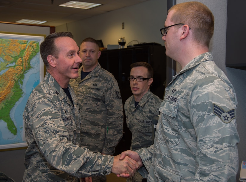 Senior Airman Kyle Alexander, 89th Operational Support Squadron/Operational Weather Squadron weather forecaster, is coined by Col. Brad Hoagland, JBA/11th Wing commander, at the weather flight office on Joint Base Andrews, Md., March 13th, 2015. The 89 OSS/OSW is being recognized for correctly forecasted eight-out-of-eight winter weather system. (U.S. Air Force photo/Airman 1st Class Philip Bryant)