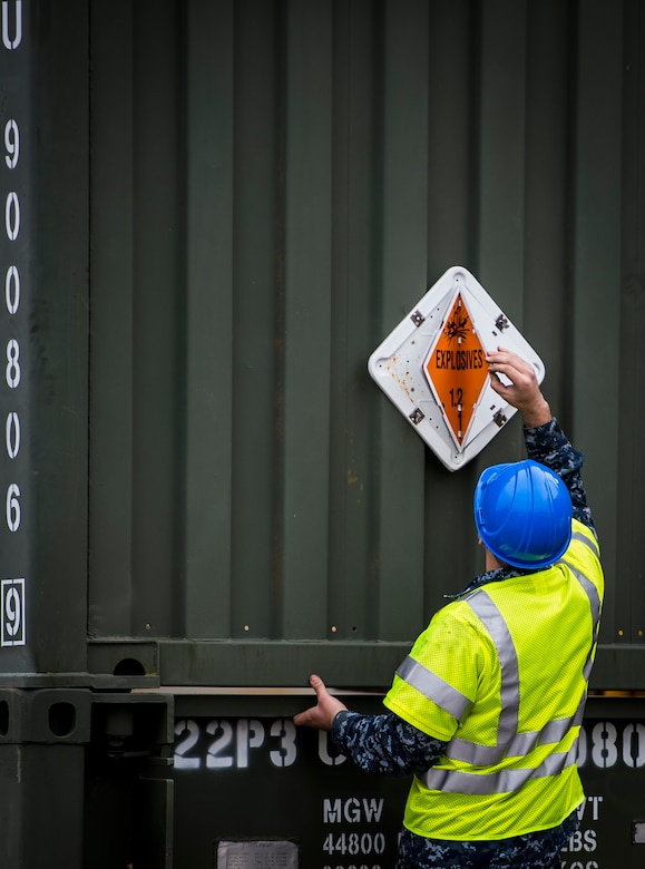 A Sailor with the Navy Munitions Command Unit Charleston adjusts an explosives warning sign March, 25, 2015, near the USNS Lewis and Clark (T-AKE-1) at Naval Weapons Station Wharf Alpha in Charleston, S.C. The Lewis and Clark is a replenishment naval vessel. In 2012, USNS Lewis and Clark became one of 14 ships that comprise the United States Marine Corps Maritime Prepositioning Program. Prepositioning ships provide quick and efficient movement of military equipment/supplies between operating areas without reliance on other nations' transportation networks. These ships give U.S. regional combatant commanders the assurance that they will have what they need to quickly respond in a crisis - anywhere, anytime. (U.S. Air Force photo/Airman 1st Class Clayton Cupit)