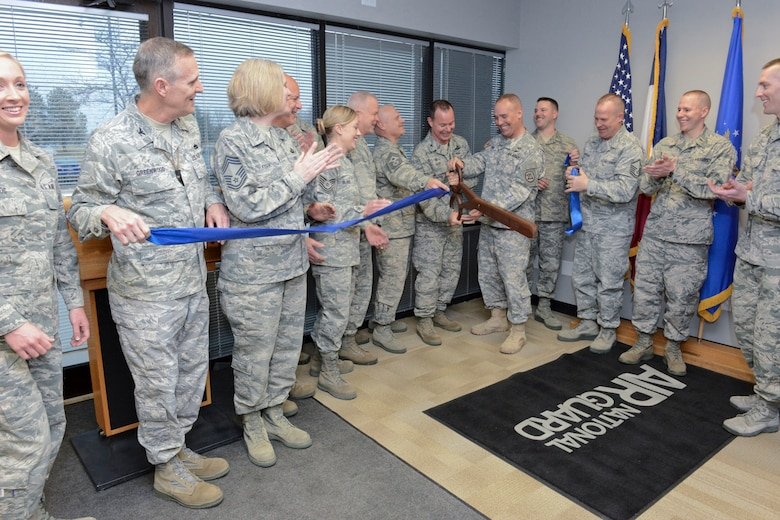 The Adjutant General of the Iowa National Guard, Maj. Gen. Timothy Orr (scissors, right), and 132d Wing (132WG) Commander, Col. Kevin Heer (scissors, left), cut the ribbon as members of the Iowa Air and Army National Guard celebrate the opening of the 132WG, Des Moines, Iowa off-site Recruiting Operation Center during a ribbon cutting ceremony held at the new Recruiting Operation Center in West Des Moines, Iowa on Tuesday, March 24, 2015.  Leaders of the Iowa National Guard, leaders of the 132WG and members of the 132WG Force Support Squadron hold the ribbon as it is being cut.  (U.S. Air National Guard photo by Staff Sgt. Linda K. Burger/Released)