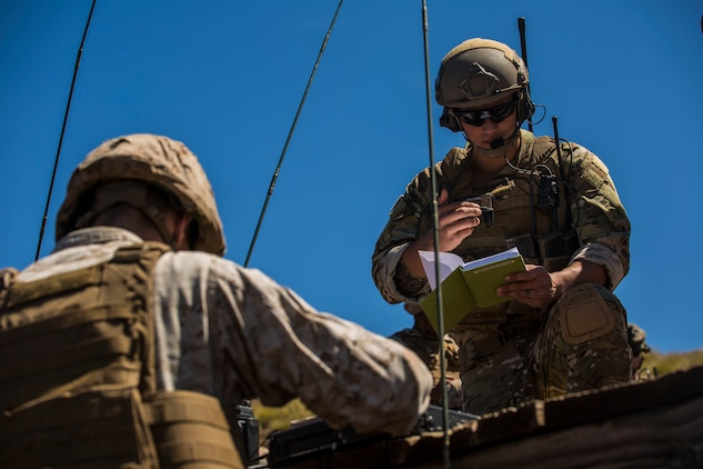 Air Force Staff Sgt. Craig R. Gabrielson (Right) works with Marine radio operators and forward observers to coordinate air assets with ground forces March 10 during Dragon Fire Exercise 15-2 at Pohakuloa Training Area, Hawaii. Marines and airmen work together to provide ultimate efficiency on the battle field with combined arms. Gabrielson, a Riverside, California, native, is a joint terminal attack controller with 25th Air Support Operations Squadron.