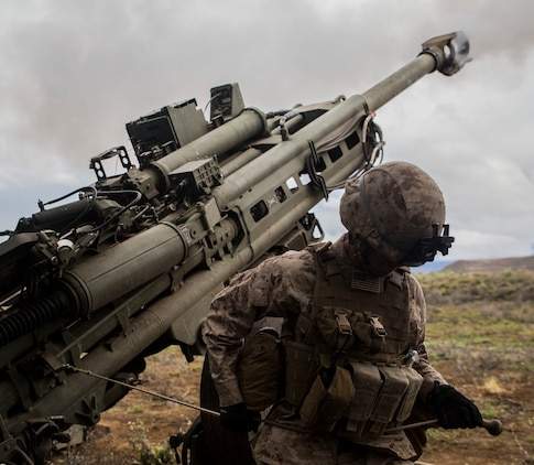 Cpl. Calvin V. Montgomery uses his whole body to pull the lanyard of an M777 Howitzer, firing a 155 mm round March 11 during Dragon Fire Exercise 15-2 at Pohakuloa Training Area, Hawaii. Howitzers are used by artillery batteries to provide suppressing fire for ground units. Montgomery, an Eatonton, Georgia, native, is a radio operator with Headquarters Battery, 12th Marine Regiment, 3rd Marine Division, III Marine Expeditionary Force.