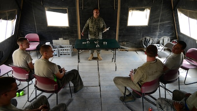 U.S. Air Force Capt. James Henry, center, 379th Air Expeditionary Wing chaplain, provides a worship service for Airmen from the 379th Expeditionary Maintenance Group at the flightline chapel, March 27, 2015, at Al Udeid Air Base, Qatar. Henry is the chaplain for the 379th EMXG and knows how difficult it is for maintenance Airmen to break away from the flightline to attend worship services, so he brings the services to them. (U.S. Air Force photo by Senior Airman Kia Atkins)