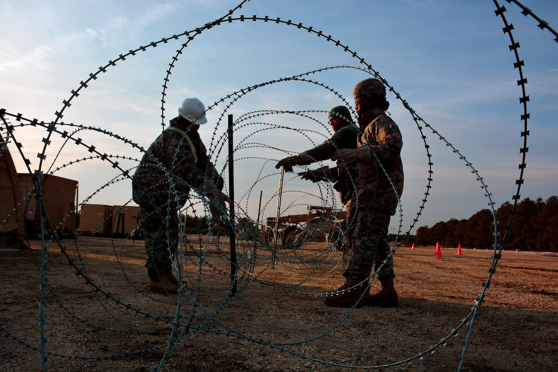 U.S. Army Soldiers from the 688th Rapid Port Opening Element, based out of Fort Eustis, Virginia, setup Concertina wire around a forward operating base, March 10, 2015, during Exercise Eagle Flag 15-2, at Joint Base McGuire-Dix-Lakehurst, New Jersey. Exercise Eagle Flag is a U.S. Air Force Expeditionary Center exercise used to execute and evaluate mobility operations and expeditionary combat support. (U.S. Air Force photo/Senior Airman Charles Rivezzo)
