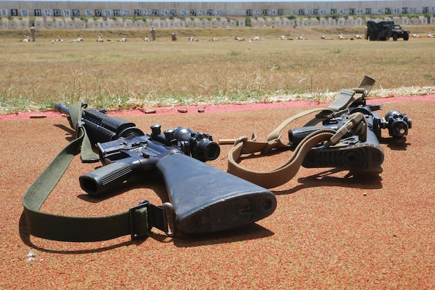 The M16A4 service rifle, donning the web sling, lies next to an M4 carbine rifle, donning the vigorous combat application sling, during annual rifle training at Puuloa Range Training Facility, March 23, 2015. All units are expected to transition from the web sling to either the VCAS sling, or the three-point sling by July 1. (U.S. Marine Corps photo by Lance Cpl. Adam O. Korolev/Released)