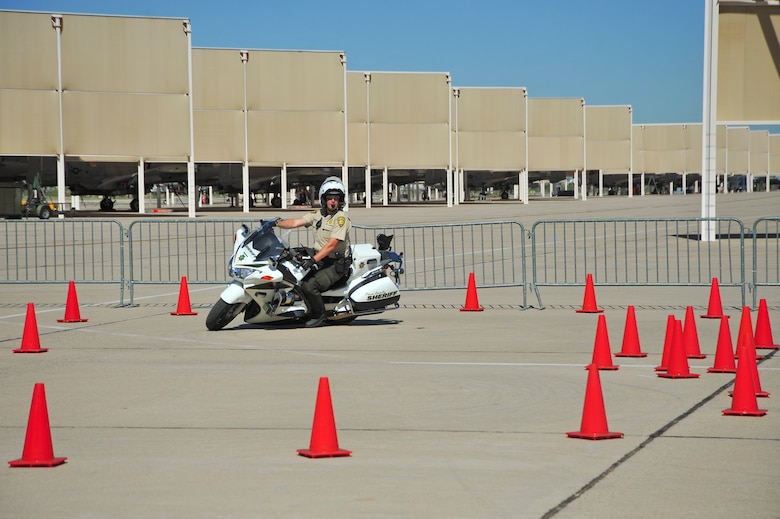 A Pima County Sheriff?s Department officer maneuvers a motorcycle inside a coned obstacle course during a motorcycle safety rally at Davis-Monthan Air Force Base, Ariz., March 27, 2015.  During the rally, the sheriff?s department conducted several demonstrations and gave driving tips to the riders who participated in their course.  (U.S. Air Force photo by Airman 1st Class Chris Massey/Released)
