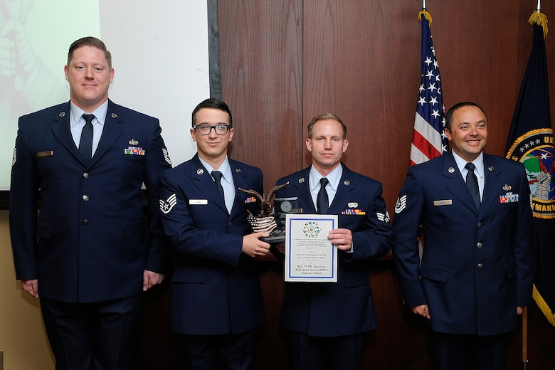 U.S. Air Force Tech. Sgt. Grady Murphy, Staff Sgt. Guy Winn, Senior Amn. Jonathon Smail and Tech. Sgt. Jeremy Gourd from the 223d Space Communication Squadron, MILSTAR Antenna Reference Unit Solution Team receive the 2014 Department of Defense Chief Information Officer Nuclear Command, Control and Communications Team Award during an Integrated Tactical Warning and Attack Assessment stakeholder's meeting, Peterson Air Force Base, Colo., Feb. 24, 2015. U.S. Navy Adm. Cecil D. Haney (not pictured), U.S. Strategic Command commander, hosted the conference and recognized the team's accomplishments in support of the nuclear enterprise by presenting its members with command coins. USSTRATCOM oversees the nation's strategic forces, including bomber, intercontinental ballistic missile and submarine forces, as well as the communication networks and sensors that tie them all together. (Photo courtesy of Duncan Wood, Air Force Space Command)