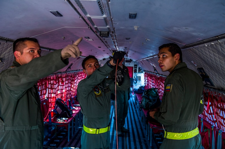 Tech. Sgt. Javier Borgesmartin, a loadmaster instructor for the 571st Mobility Support Advisory Squadron, shows Colombian Air Force loadmasters Tecnico Cuatro Javier Castillo and Sergio Leonardo Molina correct procedures for rigging a winch retriever cable on a Colombian Air Force Casa 295 aircraft in preparation for the first air drop with United States Air Force personnel aboard on March 3, 2015 at Marandua Air Force Base in Colombia, South America. (Photo by U.S. Air Force Tech. Sgt. Matthew Hannen)
