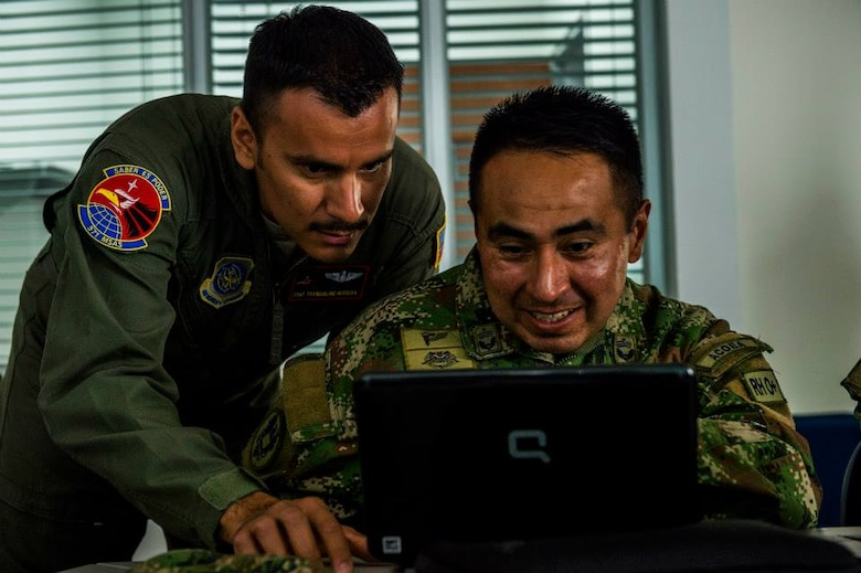 Tech. Sgt. Tranquilino Herrera, a loadmaster Air Advisor for the 571st Mobility Support Advisory Squadron, assist Colombian Air Force airmen Tecnico Primero Camilo Andres Rey with preparing a rigging checklist for the first air drop with United States Air Force personnel aboard on March 2, 2015 at CATAM Air Force Base, Colombia in South America. (Photo by U.S. Air Force Tech. Sgt. Matthew Hannen)