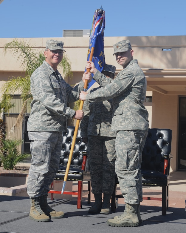 U.S. Air Force Maj. Stephen Anderson receives the 355th Force Support Squadron guidon from Col. Rodger Schuld, 355th Mission Support Group commander, during the 355th FSS change of command ceremony at Davis-Monthan Air Force Base Ariz., March 27, 2015. Anderson assumed command over the men and women of the 355th FSS. (U.S. Air Force photo by Airman 1st Class Cheyenne Morigeau/Released)