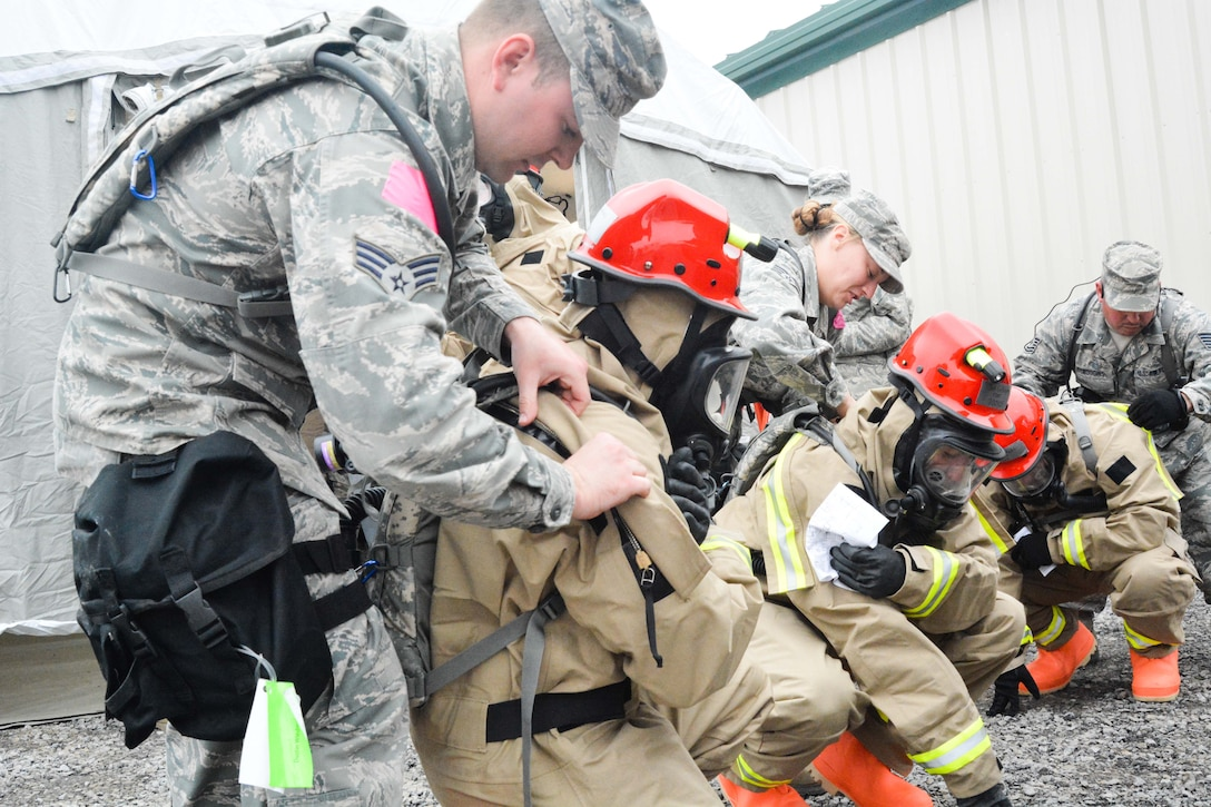 U.S. Airmen assigned to the Fatality Search and Recovery Team of the Missouri National Guard's Homeland Response Force don protective equipment at Camp Gruber in Braggs, Okla., March 19, 2015. The guardsmen were evaluated on their ability to respond to a large scale natural disaster or terrorist attack. (U.S. Air National Guard photo by Airman 1st Class Chayla Hurd/Released)