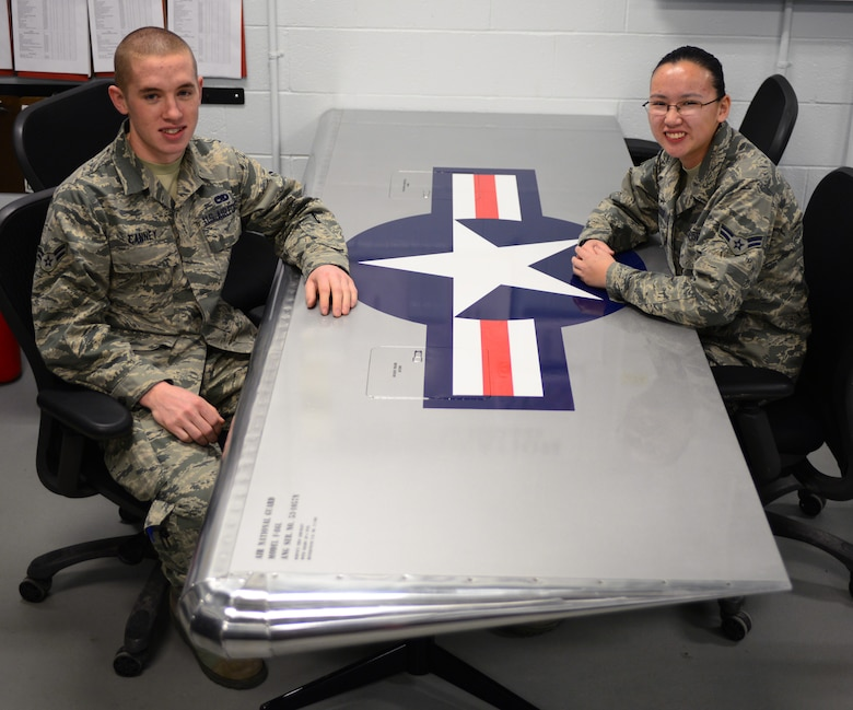 New Hampshire Air National Guard Airman First Class Kevin Canney (left) and Airman First Class Margaret Wilcox, both aircraft structural maintenance apprentices with the 157th Maintenance Group, sit at the aircraft wing shaped table they designed, built and painted March 24, 2015 Pease Air National Guard Base, N.H. They made the table to practice the skills they learned in technical school before working on actual aircraft. (New Hampshire Air National Guard photo by Airman Ashlyn J. Correia/RELEASED)