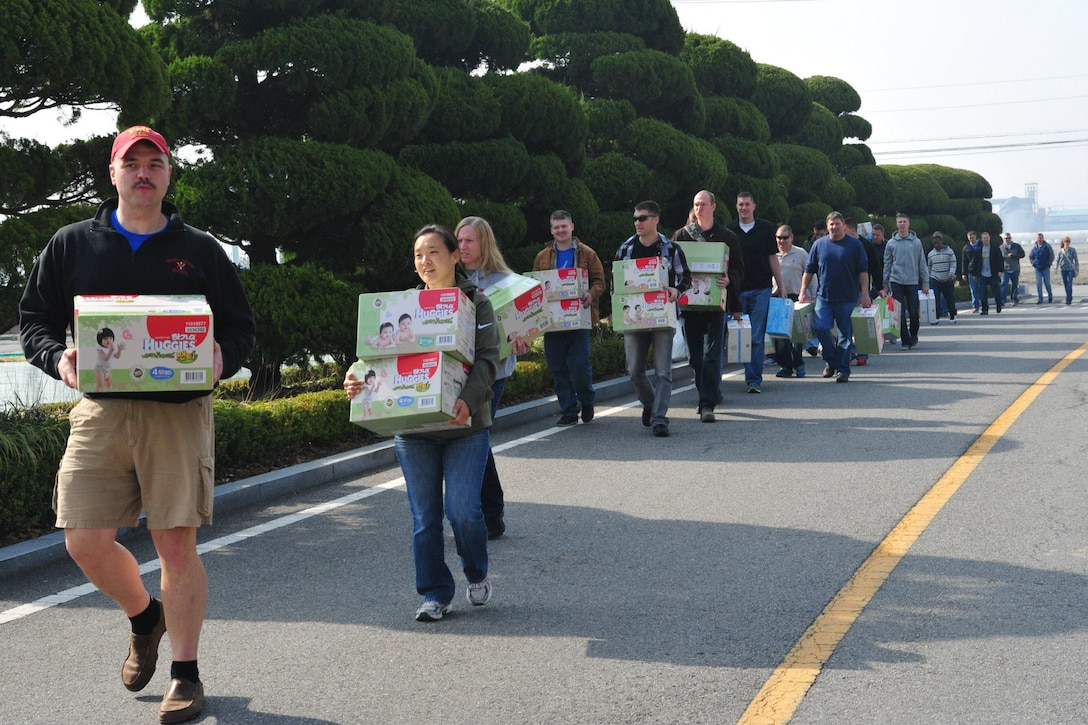 Father Edward Ramatowski (left), 8th Fighter Wing chaplain, leads 35 volunteers from Kunsan Air Base to the Moses Infant Home carrying 32 boxes of donated diapers and wet wipes in Gunsan City, Republic of Korea, March 21, 2015. Thirty-five members from the 8th Fighter Wing and the deployed 120th Expeditionary Aircraft Maintenance Unit visited the children's home to spend time with the 30 children living there. (U.S. Air Force photo by Capt. Reba Good/Released)
