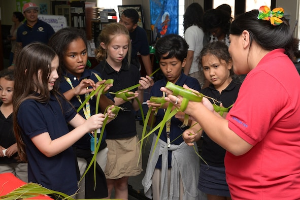 Noreen Castro, 36th Force Support Squadron administration clerk, teaches Team Andersen children how to weave palm leaves during a Chamorro Month presentation March 26, 2015, at Andersen Air Force Base, Guam. The 36th FSS hosted activities for Team Andersen children to learn about the Chamorro culture. (U.S. Air Force photo by Airman 1st Class Joshua Smoot/Released)