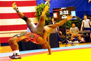 Sgt. Caylor Williams of the U.S. Army World Class Athlete Program throws PO2 Antonio Harris of the Naval Mobile Construction Battalion at Dover, Delaware, during Army's 29-4 victory over Navy in the opening session of the 2015 Armed Forces Wrestling Championships on Friday at the Army Morale, Welfare and Recreation Special Events Center on Fort Carson, Colorado. U.S. Army photo by Tim Hipps, IMCOM Public Affairs