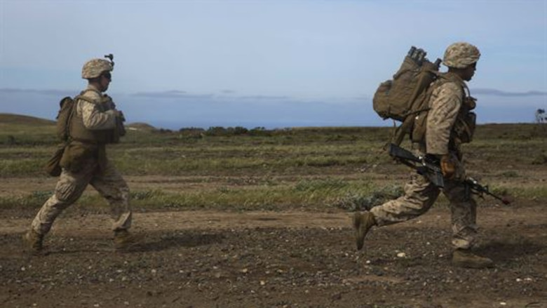 U.S. Marines with Lima Company, Battalion Landing Team 3rd Battalion, 1st Marine Regiment, 15th Marine Expeditionary Unit, run toward their objective during Composite Training Unit Exercise on San Clemente Island, California, March 22, 2015. As part of the 15th MEU's ground combat element, the Marines practiced their urban movement and room clearing skills in preparation for their deployment.