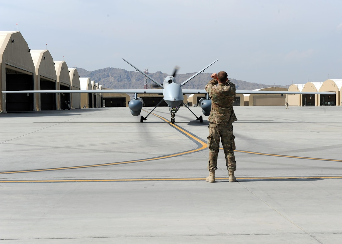 An Airman assigned to the 451st Expeditionary Aircraft Maintenance Squadron marshals an MQ-9 Reaper to the runway prior to launch March 20, 2015, at Kandahar Airfield, Afghanistan. Airmen assigned to the 451st EAMXS provide 24/7 maintenance support to the Air Force's largest Reaper unit, ensuring ground troops are supported around the clock. (U.S. Air Force photo/Staff Sgt. Whitney Amstutz)