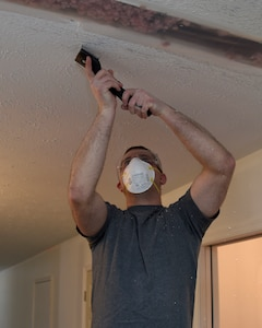 Senior Airman Tyler Ketelhut, an 89th Communications Squadron Power Pro technician, scrapes the ceiling of a home in Bowie, Md., Jan. 29, 2015. The house belongs to Tech. Sgt. Melvin Mateo, an 89th Communications Squadron Government Network Operations Center crew chief. The home is being renovated to meet requirements of his special-needs daughter. (U.S. Air Force photo/Airman 1st Class Ryan J. Sonnier)