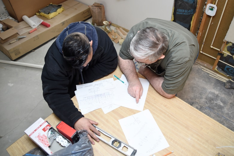 Tech. Sgt. Melvin Mateo, left, and Allen Lewey evaluate blueprints of the kitchen for Mateo's home in Bowie, Md., Jan. 29, 2015. Mateo is an 89th Communications Squadron Government Network Operations Center crew chief and Lewey is a Church of Jesus Christ of Latter-day Saints missionary. (U.S. Air Force photo/Airman 1st Class Ryan J. Sonnier)