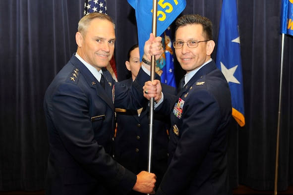 U.S. Air Force Lt. Gen. Chris Nowland, 12th Air Force commander, hands the 557th Weather Wing guidon to U.S. Air Force Col. William Carle, 557th Weather Wing commander, as part of the Air Force Weather Agency's re-designation to the 557th WW March 27 at the Lt. Gen. Thomas S. Moorman building, Offutt Air Force Base, Nebraska. The Wing, previously a Field Operating Agency, will now fall under Air Combat Command and the 12th Air Force. (U.S. Air Force photo by Jeff Gates/Released)