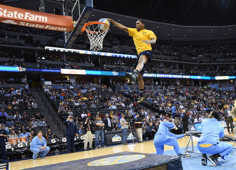 A U.S. Navy member dunks a basketball during the Hoops for Troops Night with the Denver Nuggets March 27, 2015, at the Pepsi Center in Denver. Hoops for Troops Night is held to honor military men and women with discounted ticket pricing, a halftime dunk contest and recognition of past, present and future military personnel from all branches. (U.S. Air Force photo by Airman 1st Class Samantha Saulsbury/Released)
