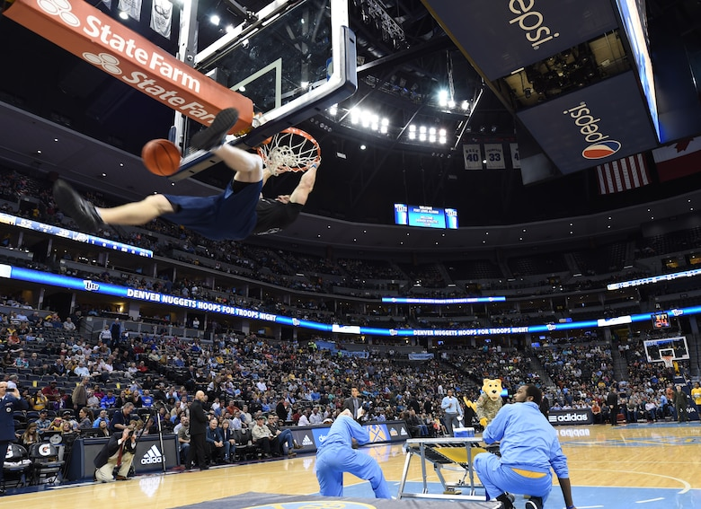 A military member dunks a basketball during Hoops for Troops Night with the Denver Nuggets March 27, 2015, at the Pepsi Center in Denver. Hoops for Troops Night is held to honor military men and women with discounted ticket pricing, a halftime dunk contest and recognition of past, present and future military personnel from all branches. (U.S. Air Force photo by Airman 1st Class Samantha Saulsbury/Released)