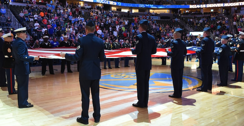 Military members unfurl the American Flag during the national anthem at the Hoops for Troops Night with the Denver Nuggets March 27, 2015, at the Pepsi Center in Denver. Hoops for Troops Night is held to honor military men and women with discounted ticket pricing, a halftime dunk contest and recognition of past, present and future military personnel from all branches. (U.S. Air Force photo by Airman 1st Class Samantha Saulsbury/Released)