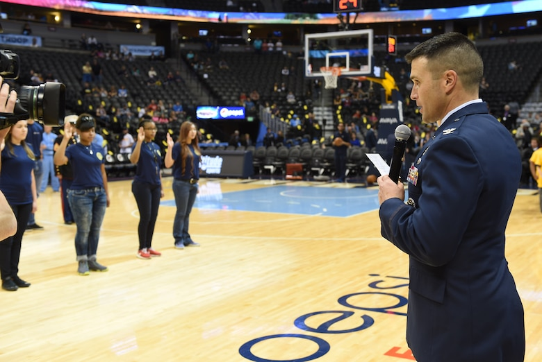 Col. John Wagner, 460th Space Wing commander, gives the oath of enlistment to recruits at the Hoops For Troops Night with the Denver Nuggets March 27, 2015, at the Pepsi Center in Denver. Hoops for Troops Night is held to honor military men and women with discounted ticket pricing, a halftime dunk contest and recognition of past, present and future military personnel from all branches. (U.S. Air Force photo by Airman 1st Class Samantha Saulsbury/Released)