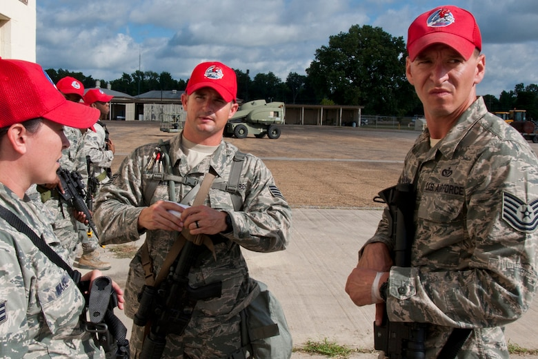 Staff Sgt. Kenneth McMillen, (center), a structural carpenter assigned to the 307th RED HORSE Squadron, instructs a group of Airmen on proper procedures for clearing buildings during a training exercise at Barksdale Air Force Base, La., Sept. 10, 2014. McMillen, who is also a Bowie County Sheriff's deputy, has been credited with saving the life of a woman in a house fire on March 9, 2015. (U.S. Air Force photo/Master Sgt. Jeff Walston)