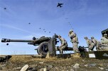 Paratroopers move an 105-mm howitzer into firing position as other paratroopers conduct a parachute assault during Operation Spartan Valkyrie at Malamute drop zone on Joint Base Elmendorf-Richardson, Alaska, March 20, 2015.
