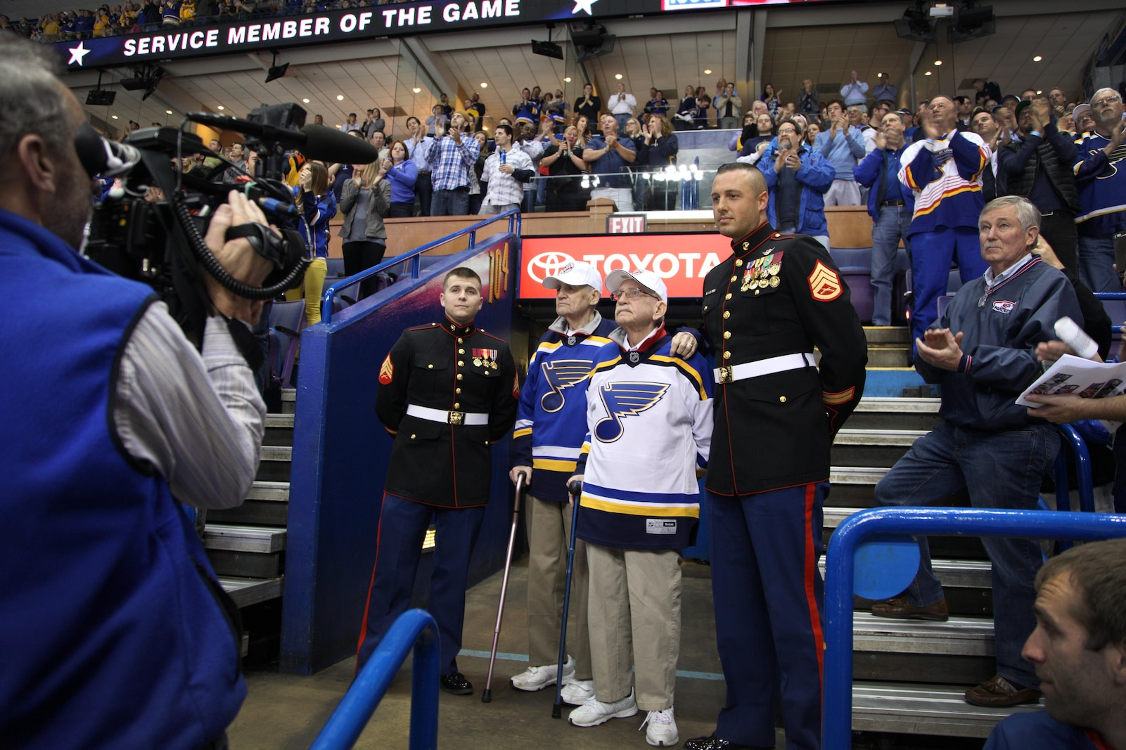 Lloyd, left, and Bill Rupp are honored as the USO Service Members of the game during a St. Louis Blues hockey game March 30 at Scott Trade Center in St. Louis. The twin brothers enlisted in 1942 into the Marine Corps and served throughout the Pacific. Lloyd was a rear gunner on a Douglas SBD dauntless dive bomber and Bill was an anti-aircraft gunner. Both served four years in the Marine Corps during WWII and settled back in St. Louis. SSgt. Derek Krause, right, is the Pool Program Specialist and Sgt. Cody Tubbs is the Operations Clerk for Recruiting Station St. Louis.