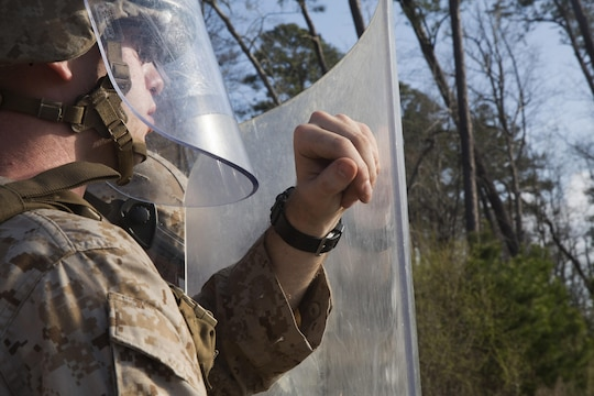 A Marine with 2nd Battalion, 6th Marine Regiment, waits for the command to rush forward during a non-lethal weapons training exercise aboard Camp Lejeune, N.C., March 25, 2015. The Marines participated in a two-week NLW course that teaches various riot-control methods.
