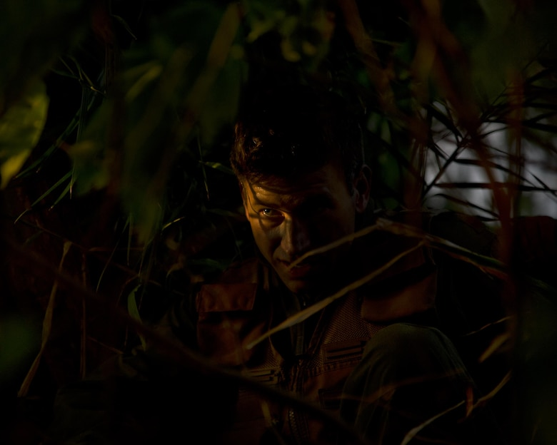Maj. Dan Allen takes cover in the brush during combat survival training March 26, 2015, at Joint Base Pearl Harbor-Hickam, Hawaii. Allen, who is a pilot evaluator for the 96th Air Refueling Squadron, led a team of four during four hours of training that is designed to simulate the aircrew going down in a hostile environment. The aircrew uses teamwork to conceal their location, evade opposition forces and practice proper recovery procedures. (U.S. Air Force photo/Tech. Sgt. Aaron Oelrich)