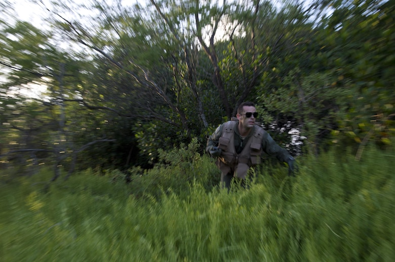 Senior Airman Kenneth Stricker runs from cover during combat survival training March 26, 2015, at Joint Base Pearl Harbor-Hickam, Hawaii. This training simulates the aircrew going down in a hostile environment. The aircrew uses teamwork to conceal their location, evade opposition forces and practice proper recovery procedures. Stricker is a boom operator for the 96th Air Refueling Squadron. (U.S. Air Force photo/Tech. Sgt. Aaron Oelrich)