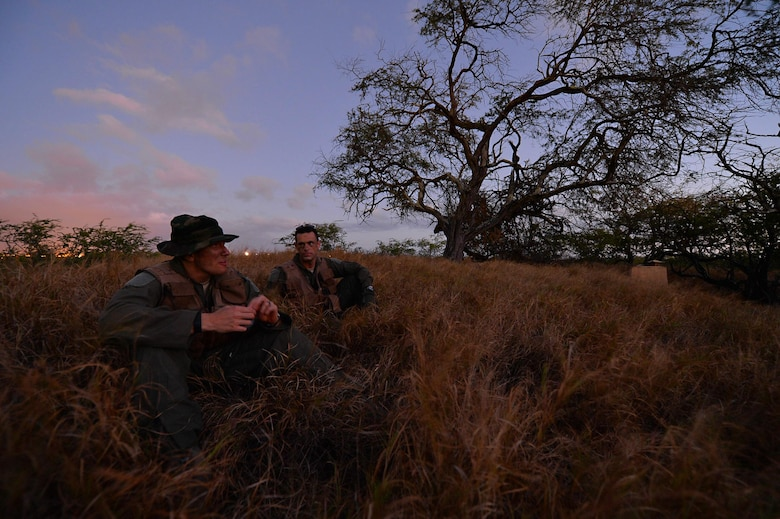 Capt. Matt Savage and Senior Airman Kenneth Stricker wait for two team members to return during combat survival training March 26, 2015, at Joint Base Pearl Harbor-Hickam, Hawaii. This training simulates the aircrew going down in a hostile environment. The aircrew uses teamwork to conceal their location, evade opposition forces and practice proper recovery procedures. Savage is a pilot and Strickler is a boom operator for the 96th Air Refueling Squadron. (U.S. Air Force photo/Tech. Sgt. Aaron Oelrich