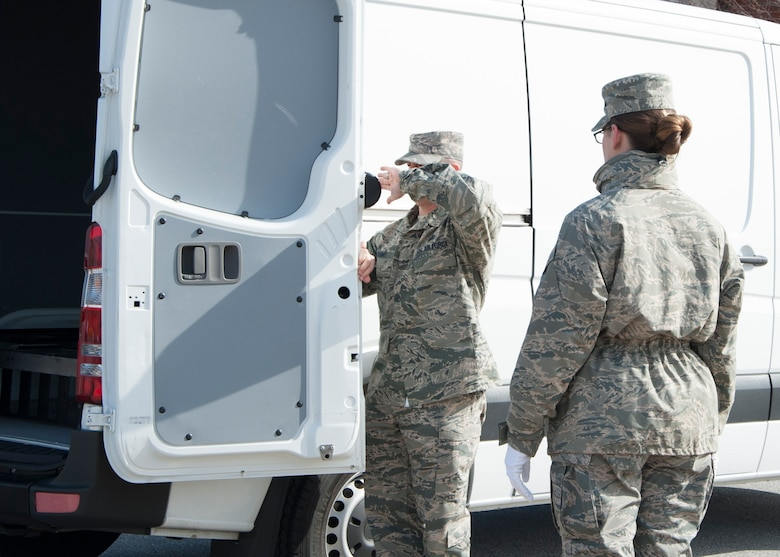 Senior Master Sgt. Brian Denny, Air Force Mortuary Affairs Operations superintendent, demonstrates to Senior Airman Jamie Debbrecht, a 512th Memorial Affairs Squadron reservist deployed to AFMAO, the proper method to shut a transfer vehicle's door March 19, 2015, at New Castle Air National Guard Base, Del. Airmen drove the van to New Castle, where it served as the transfer vehicle in the dignified transfer divert exercise, which tested AFMAO's capability to perform a DT at an alternate site. (U.S. Air Force photo/Senior Airman Jared Duhon)