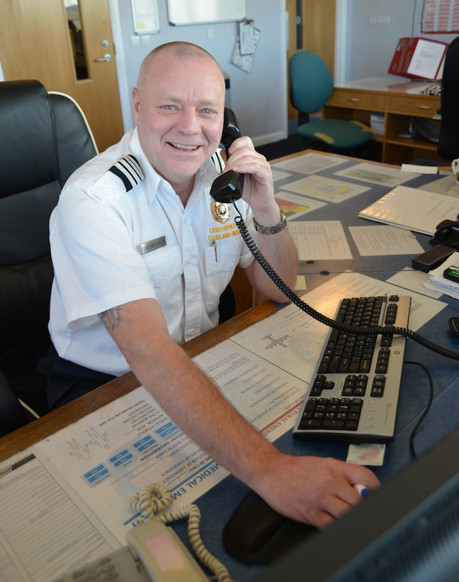 "Paul Charland-Marlow, 100th Civil Engineer Squadron Fire Emergency Services emergency control center lead dispatcher from Beck Row, Suffolk, poses for a photo in the ECC Feb. 17, 2015, on RAF Mildenhall, England. Charland-Marlow is in charge of a team of dispatchers, who he refers to as ""the voice in the dark,"" the vital link between someone calling in a 911/999 call and emergency services arriving on scene. (U.S. Air Force photo by Karen Abeyasekere/Released) (Editor's note: CAC blurred for operational security purposes)"