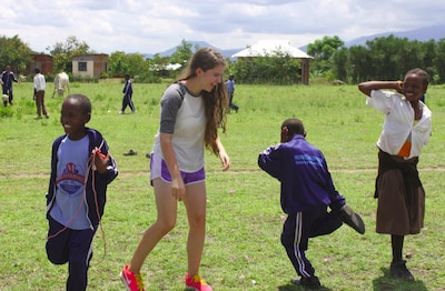 Sarah Hesterman dances with children from Tanzania during her visit to help construct schools for orphaned youth. (Courtesy Photo)
