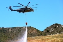 A CH-53E Super Stallion with Marine Heavy Helicopter Squadron 466, 3rd Marine Aircraft Wing, drops water onto a mock fire area during an aerial firefighting exercise here, April 30. Aviation and ground units from Camp Pendleton, 3rd MAW, Navy Region Southwest, the California Department of Forestry and Fire Protection, and the San Diego Sheriff's Department participated in the annual exercise, which provides ready, trained and certified military and civilian resources to combat wild land fires in the region.