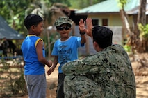 U.S. Navy Construction Mechanic 3rd Class Brian Lanasa, with  Naval Mobile Construction Battalion 5, high fives a child during a ribbon cutting and turnover of school buildings ceremony at Santa Lordes High School in Puerto Princesa, on the island of Palawan, Philippines, April 29. The construction was part of humanitarian and civic action projects during exercise Balikatan 2015. This year marks the 31st iteration of the exercise, which is an annual Philippines-U.S. military bilateral training exercise and humanitarian civic assistance engagement.